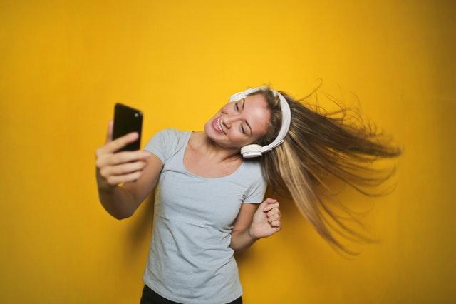 Tančící dívka s mobilem v ruce a sluchátky na uších