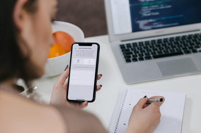 Žena opisující údaje z mobilu do zápisníku
